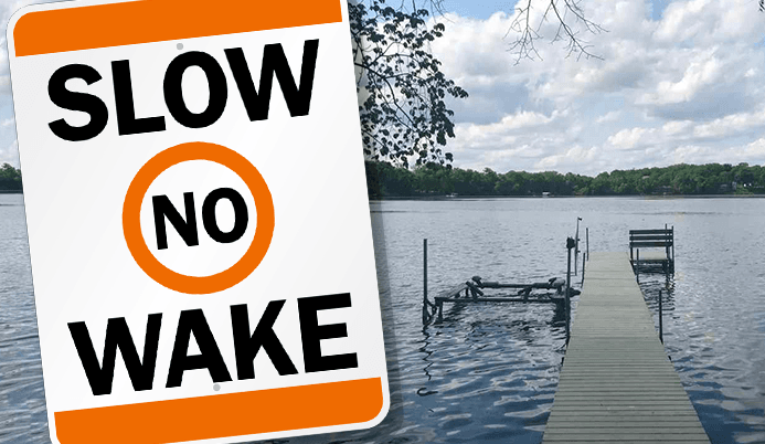 Dock on a lake with a sign that says Slow No Wake