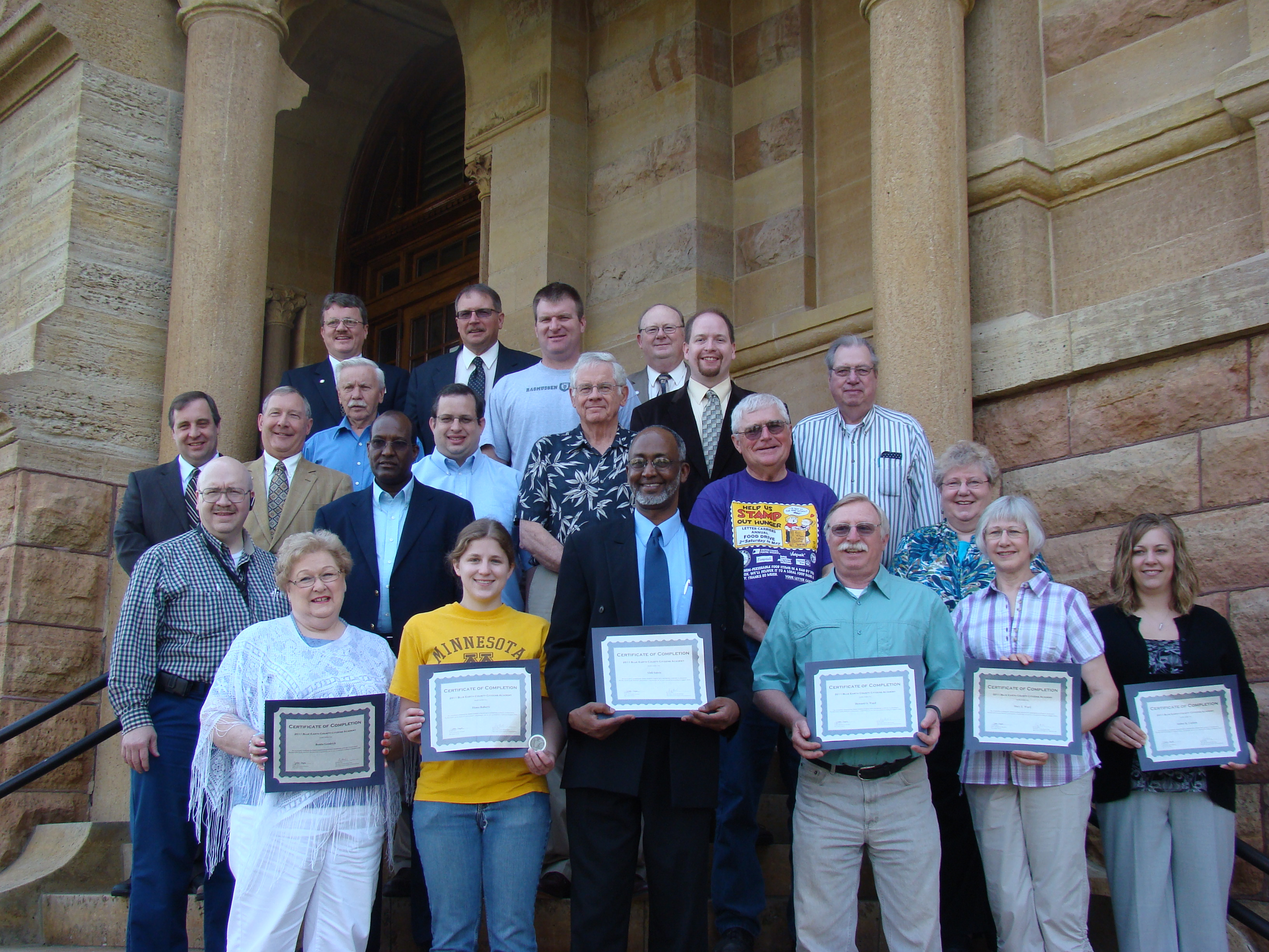 A group of graduates pose with their certificates on graduation day with the Board of Commissioners.