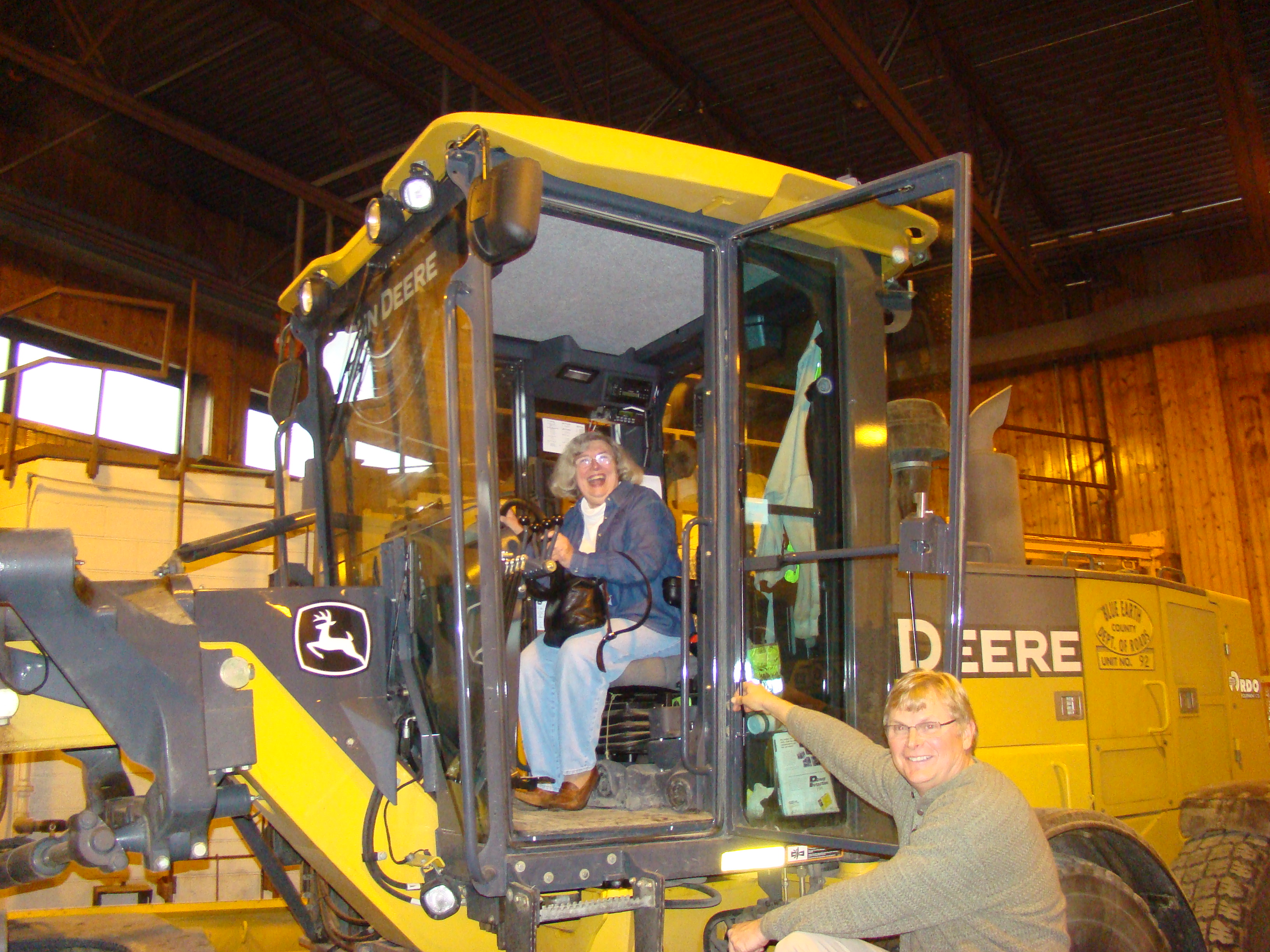 Dean Ehlers, Parks Supervisor helps a Citizens Academy participant try out sitting in a road grader.