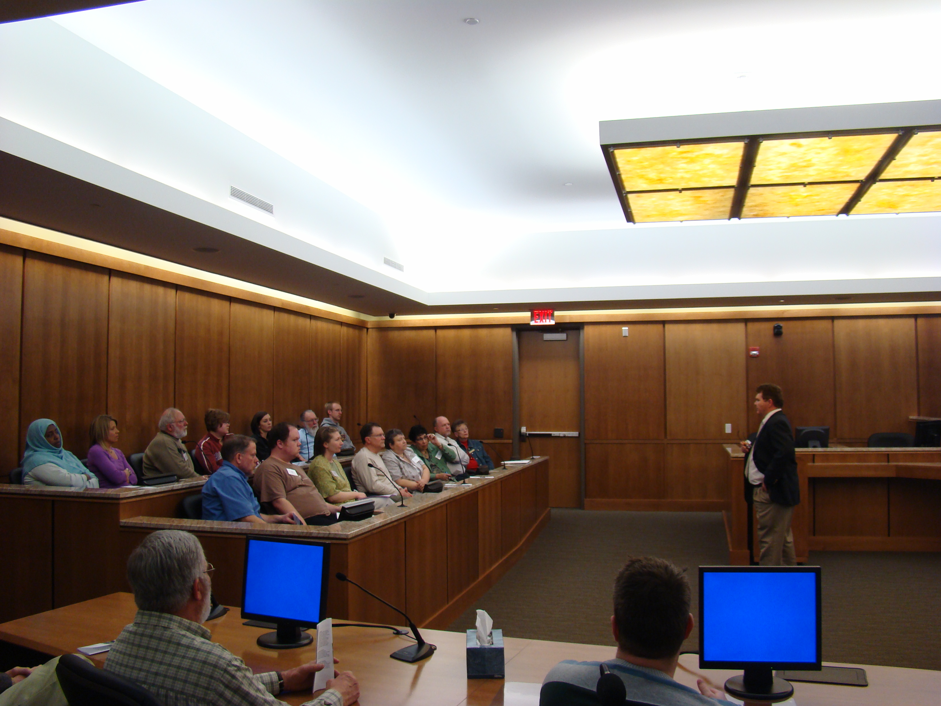 County Attorney Ross Arneson presents to the Citizens Academy group in a court room.